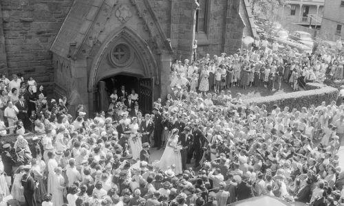 12 września 1953 r. Setki osób stało w tłumie przed stuletnim kościołem św. Marii w Newport, aby zobaczyć ślub senatora Johna F. Kennedy'ego z jego narzeczoną Jacqueline Lee Bouvier. Senator Massachusetts jest synem byłego ambasadora na dworze św. Jakuba, Josepha P. Kennedy'ego. Fot. Getty Images