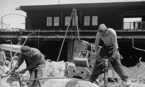 Robotnicy z młotami pneumatycznymi kruszą betonowe elementy. W tle hala prowizorycznego dworca, pełniącego funkcje Dworca Centralnego przed ukończeniem budowy. Maj 1974. Fot. NAC, Archiwum Grażyny Rutowskiej. Sygnatura: 40-W-89-28