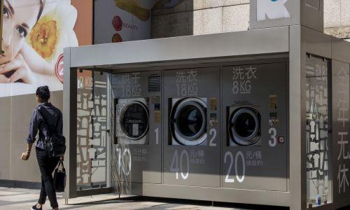 """Uliczna pralnia przy placu handlowym dzielnicy Xuhui w Szanghaju, maj 2017 r. Chiny. Na """"przystanku"""" znajdują się dwa modele pralek o różnej pojemności – 18 i 8 kg – oraz suszarka. Można za nie płacić gotówką lub za pośrednictwem WeChat czy Alipay. Fot. Visual China Group via Getty Images"""