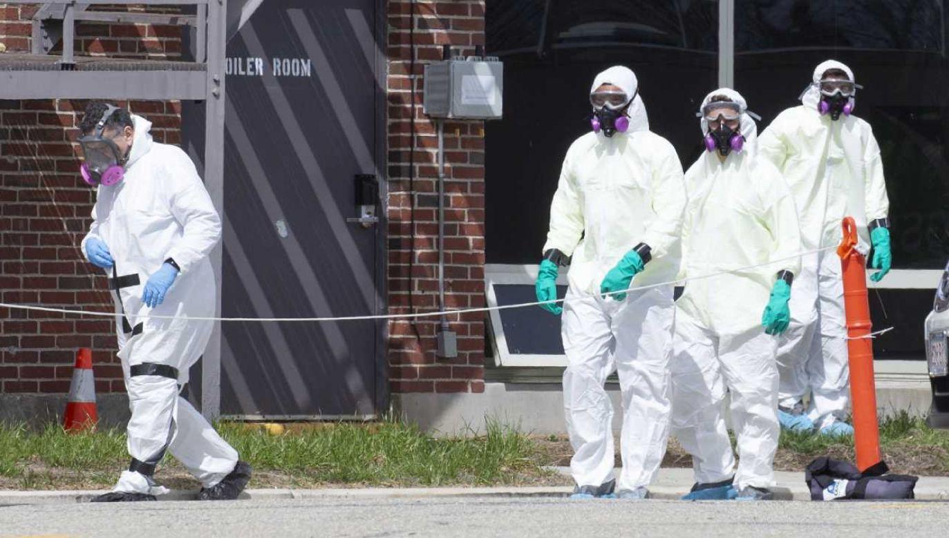 Ekipa  dezynfekująca w kombinezonach przeciwchemicznych (fot. PAP/EPA/CJ GUNTHER)