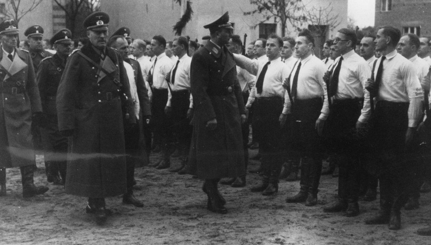 """V kolumna często składała się z osób legalnie działających w II RP organizacjach mniejszości niemieckiej. Na zdjęciu: Uroczystość  """"dnia wolności"""" w Środzie Wielkopolskiej obchodzonego 5 listopada 1939 roku z udziałem Artura Greisera, namiestnika Kraju Warty. Greiser przechodzi przed szpalerem organizacji paramilitarnej Selbstschutz. Fot. NAC"""