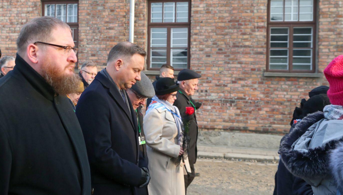 Byli więźniowie oraz prezydent RP Andrzej Duda (2L) i dyrektor Państwowego Muzeum Auschwitz-Birkenau Piotr Cywiński (L) przechodzą przez Bramę Śmierci byłego obozu Auschwitz II-Birkenau w Oświęcimiu (fot. PAP/Andrzej Grygiel)